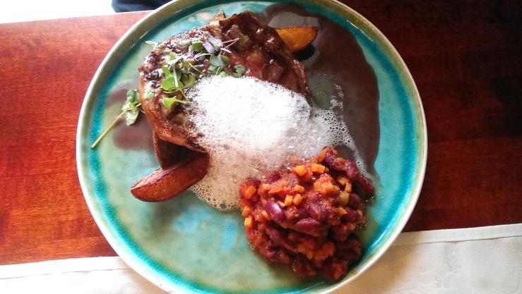 Говяжий стейк на гриле с пряными бобами и винным соусом. Grilled beef steak with spicy beans and wine sauce.